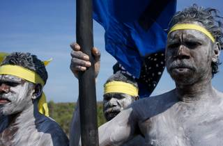 First Nations men in traditional paint and headscarves