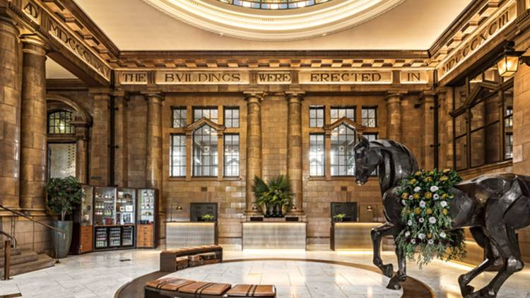 Hotel lobby with domed glass ceiling and large horse statue
