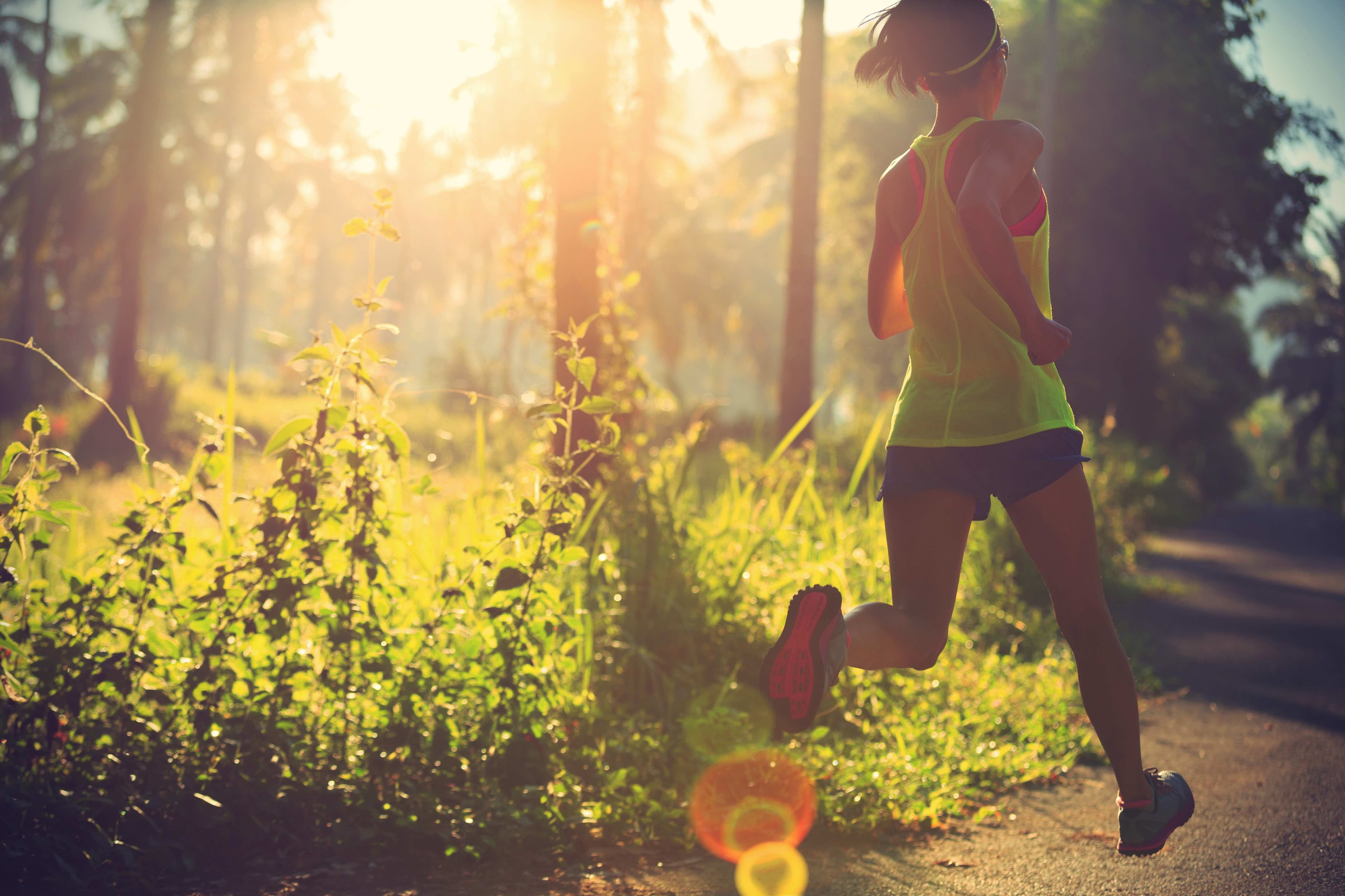 Young,Fitness,Woman,Running,At,Morning,Tropical,Forest,Trail