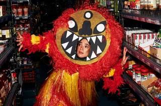 A person peers out from a gold and red costume in a grocery aisle