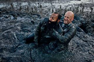 Two men wearing suits wrestle in a muddy pool