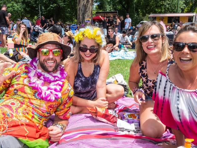Colourfully dressed people in sunglasses, floral necklaces and head pieces smile at the camera as they sit on the grass in the sun.