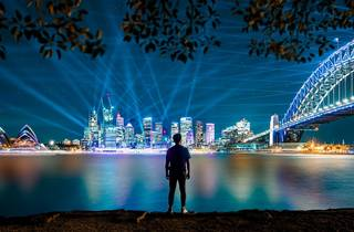 A man watching the Vivid Sydney lights from across the hardbour