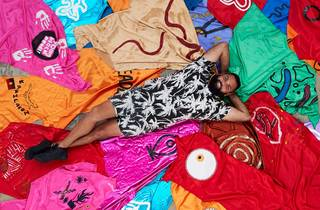 First Nations artist Dennis Golding lies on a bed of superhero capes designed by school kids
