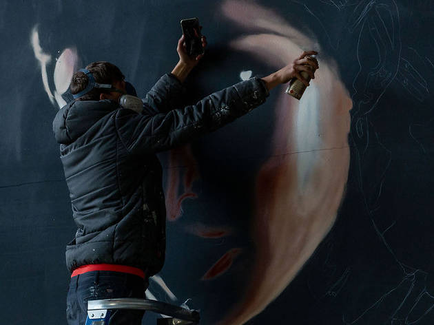 A man wearing a dark hooded jacket and a respiration mask created a mural of a woman's face using aerosol paint