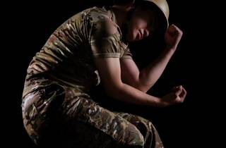 a soldier ln uniform lies curled in the foetal position