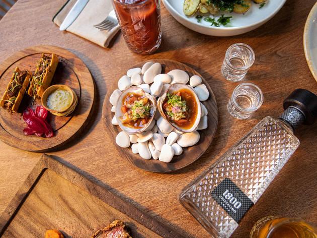 Mesa de restaurante con platillos servidos y botella de tequila