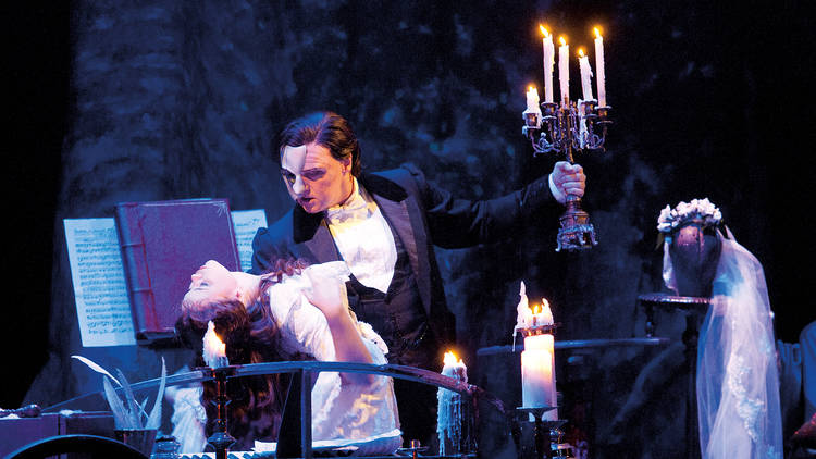 A man wearing a white mask over half his face holds an ornate candlestick in one hand and a swooning woman in a long white dress in the other