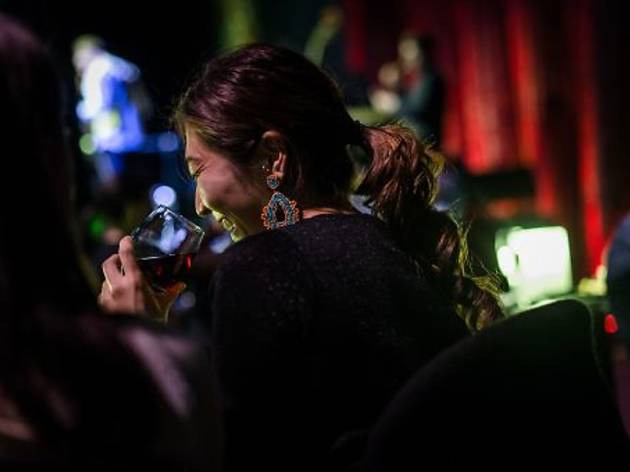 A woman smiles in a dark room while going to drink from a glass