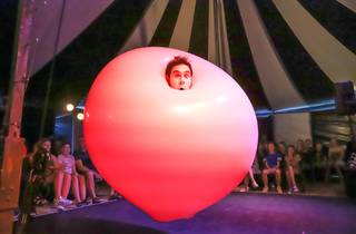 A man's face emerges from a giant pink bubble with an impressed audience in the background