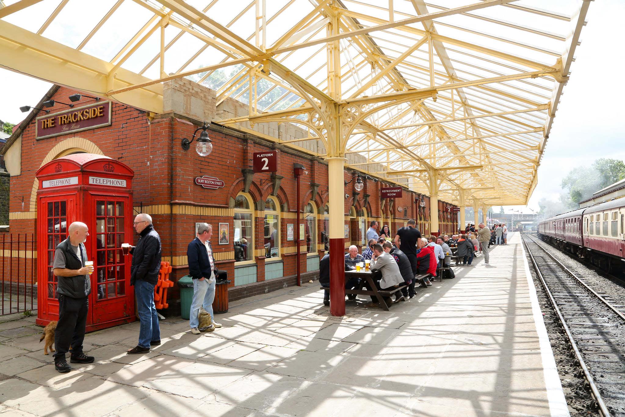 People drinking on a train station platform