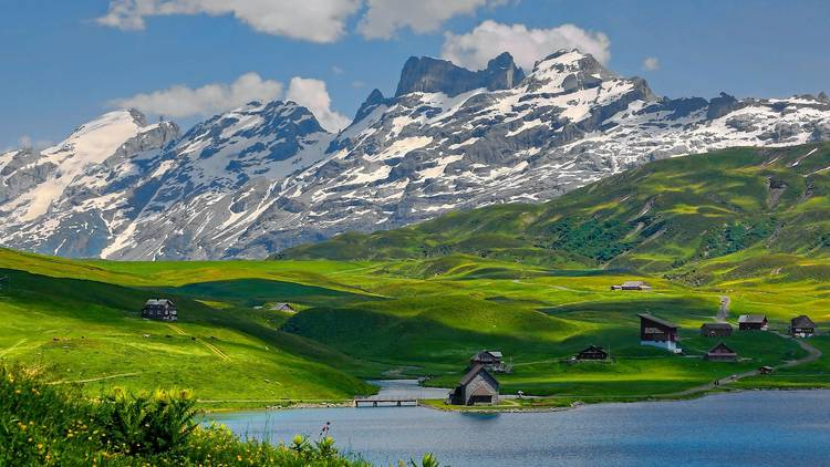 Mountains, grassy green hills and a lake in Switzerland.