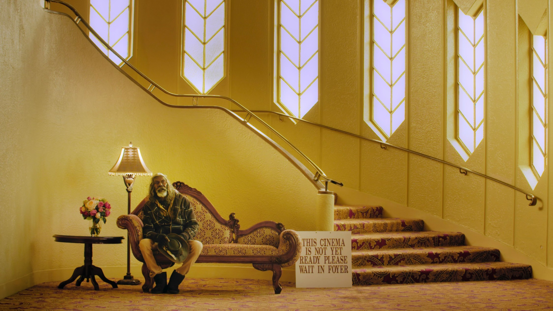 Esteemed actor David Gulpilil sits in the honey-coloured  foyer of an old cinema