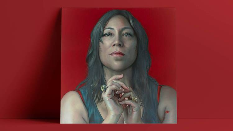 A portrait of singer Kate Ceberano on a dramatic blood-red backdrop