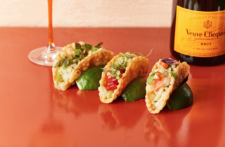 Pinchy's tacos rested against lime wedges on a shiny red tabletop with a bottle of Veuve Clicquout in the background