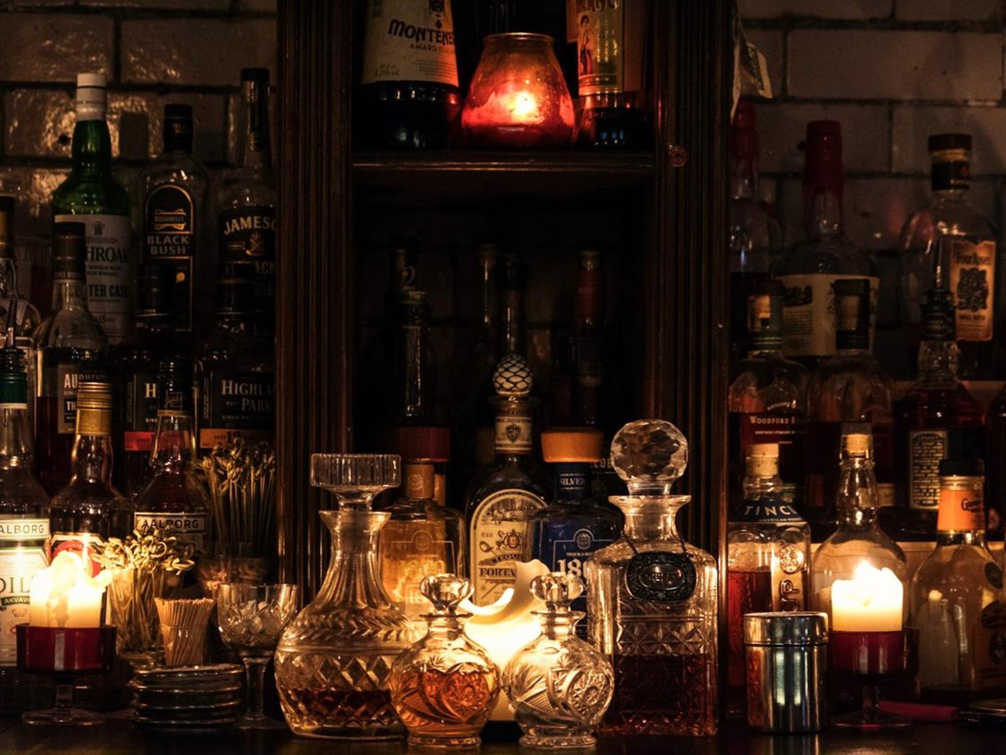 A dimly lit bar in candlelight with a selection of bottles and glasses