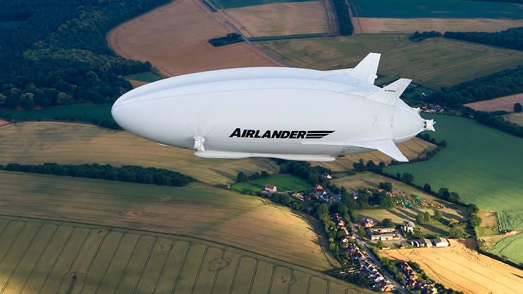 Airlander 10 hybrid-electric blimp in the air over green fields