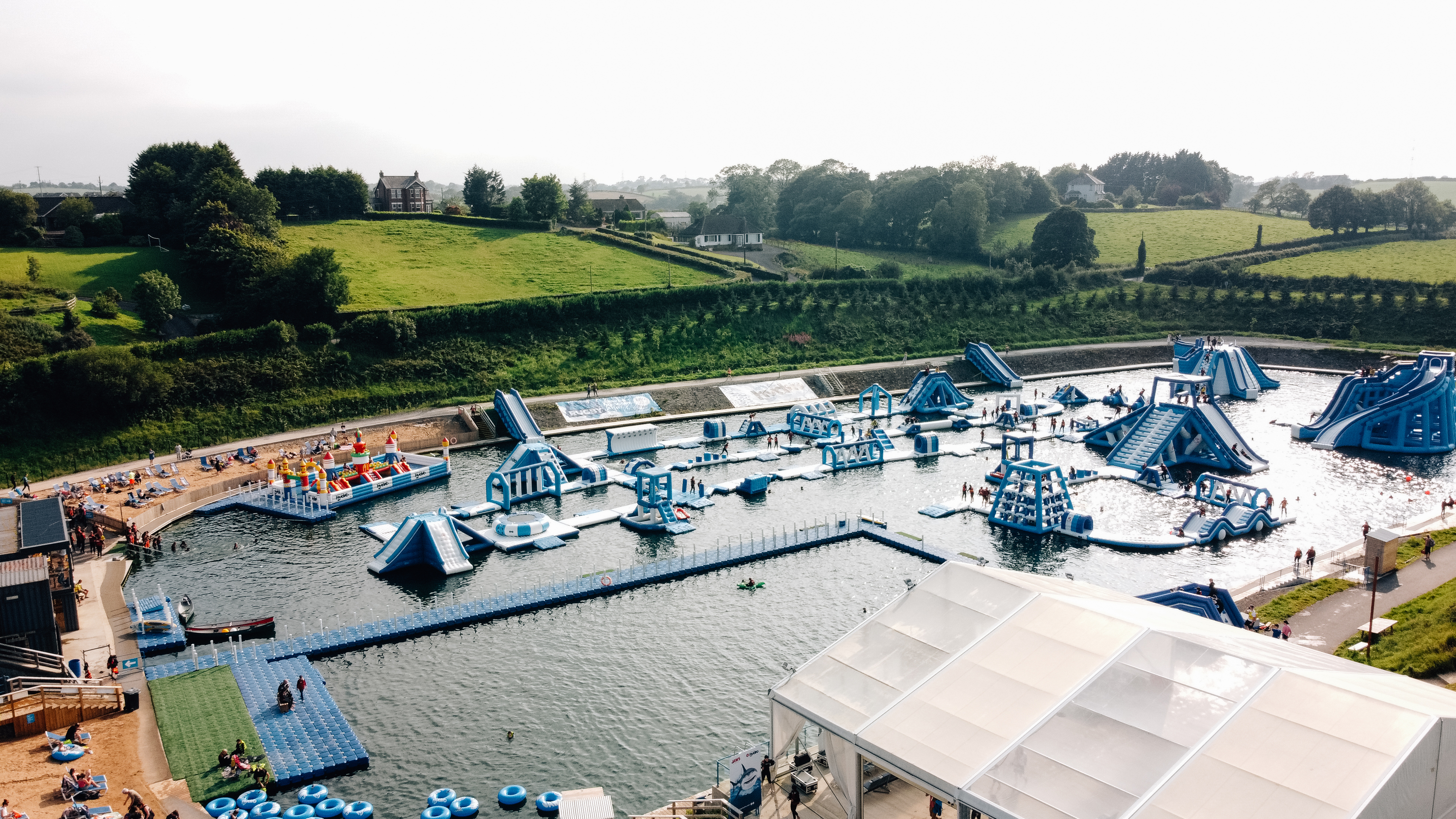 Let's Go Hydro, nn inflatable adventure playground floating on Belfast's Knockbracken Reservoir, surrounded by green fields and trees