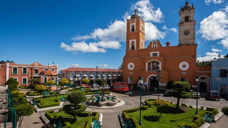 Toma abierta de plaza con jardines e iglesia