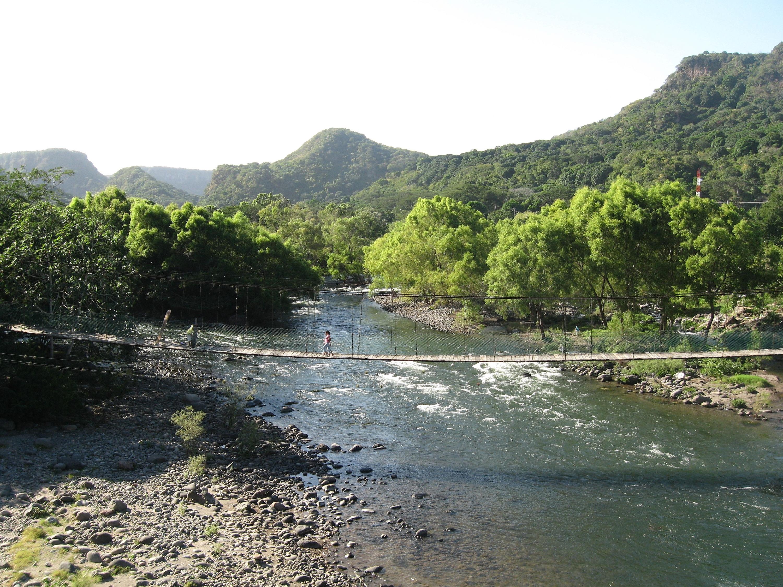 Toma abierta de río con puente colgante