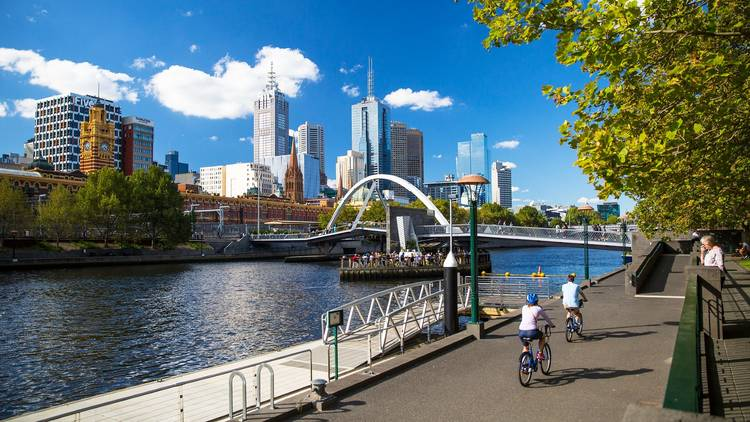 Two people rides bikes next to the Yarra River in Melbourne's CBD, near Ponyfish Island.