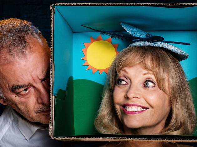 A woman wearing a fascinator is in a box, with a man looking on