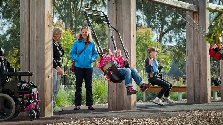 Kids playing in swings while parents watch on