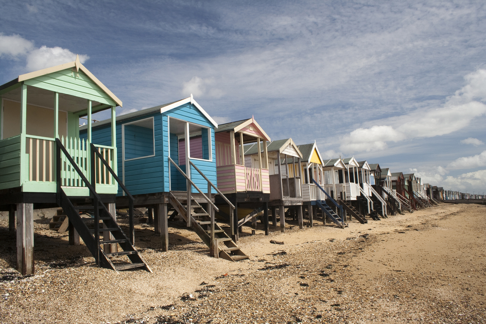 A row of colourful beach huts with small ladders descending onto a sandy beach at Thorpe Bay, Southend-on-Sea