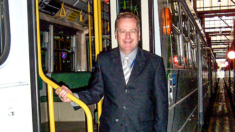 Colin Tyrus, voice of Melbourne trams, standing in the stairwell of an old style melbourne tram at a depot
