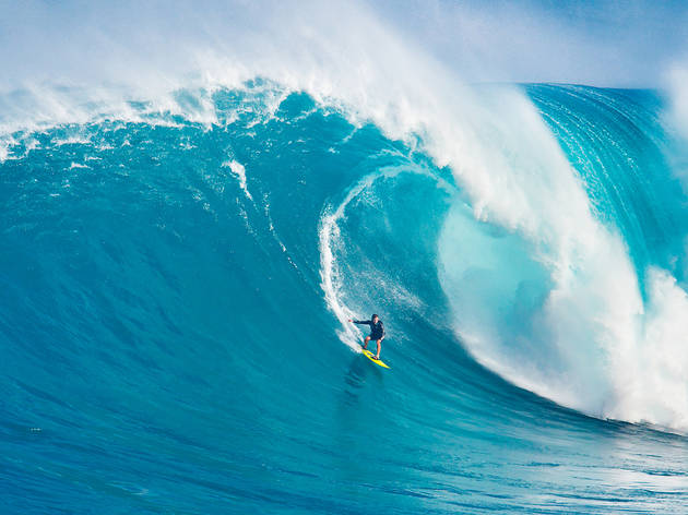 Professional surfer Carlos Burle rides a giant wave in Maui, HI.