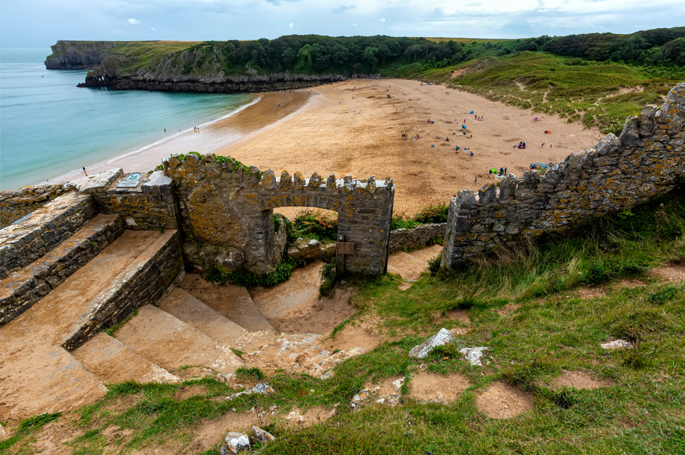 A shot of stone steps descending through a ruined stone archway to the yellow sand of Barafundle Bay, with the blue ocean on the left and grassy banks to the right of the beach