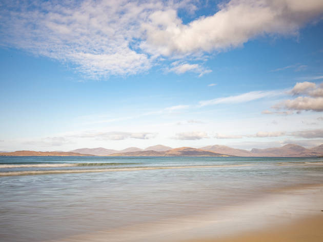 Long exposure shot of Scarista beach, with yellow sand in the foreground, blurry water stretching into the distance, faded mountains in the background and a blue cloudy sky overhead