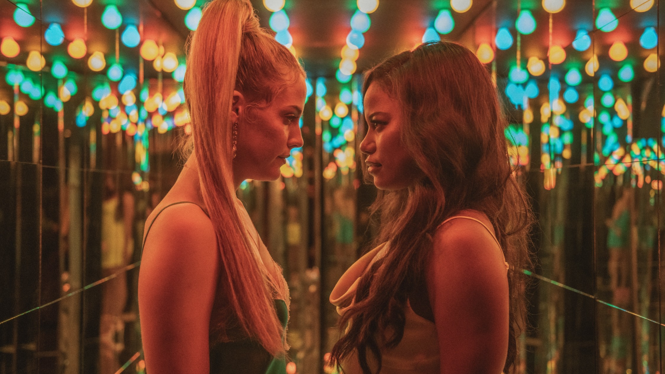 Two women stare at each other bathed by neon light