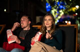 a man and a woman watch movies with popcorn