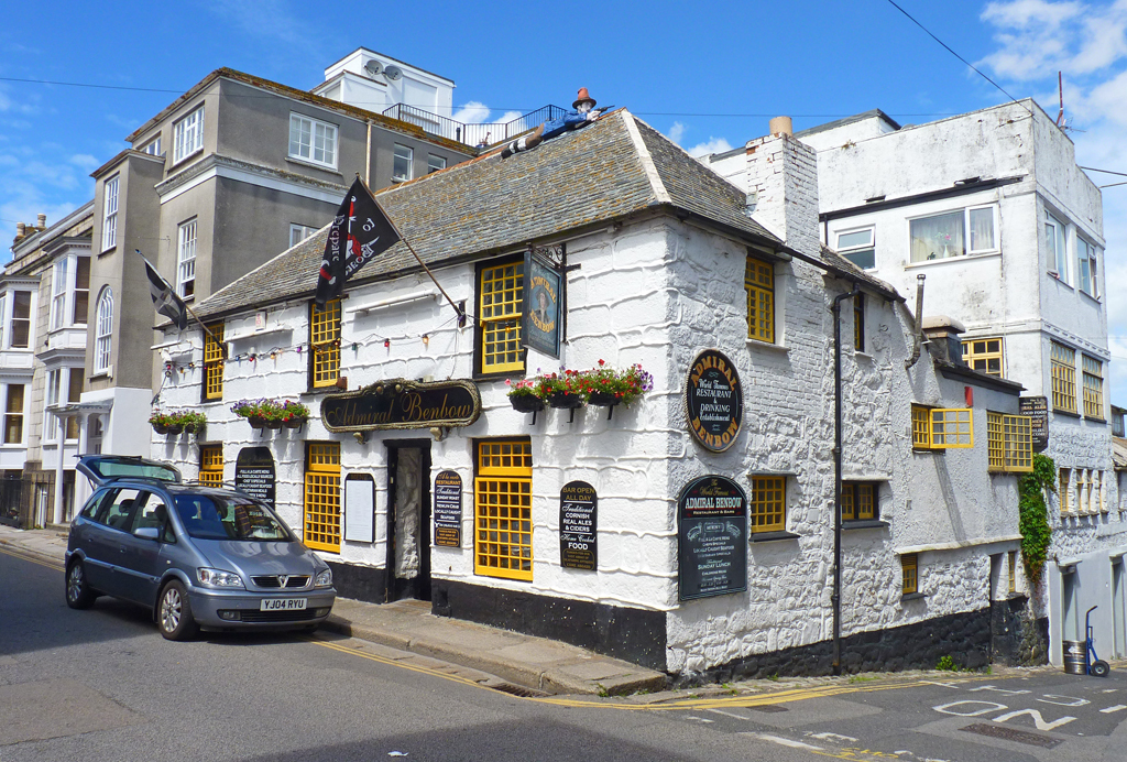 An outside view of a pub painted white with yellow window frames