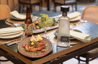 Pulpo servido en plato en una mesa con botella de tequila y cerveza al fondo