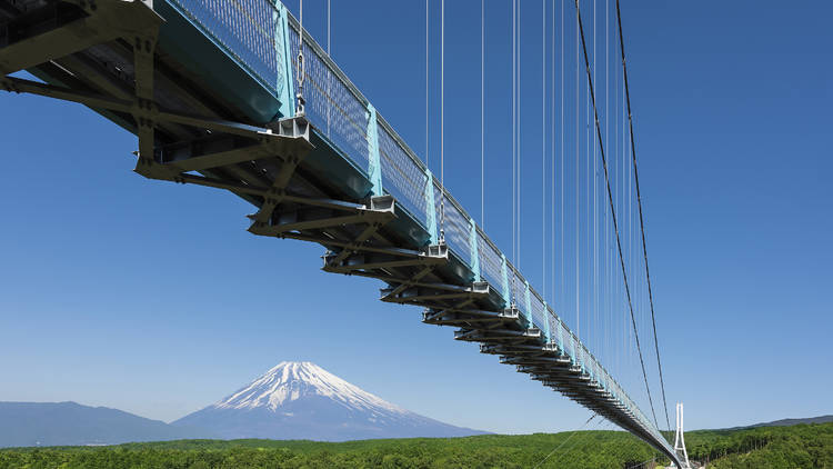 A suspension bridge over a green valley with Mt Fuji in the background