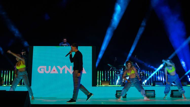 Escenario con luces azules y el cantante Guaynaa con microfono