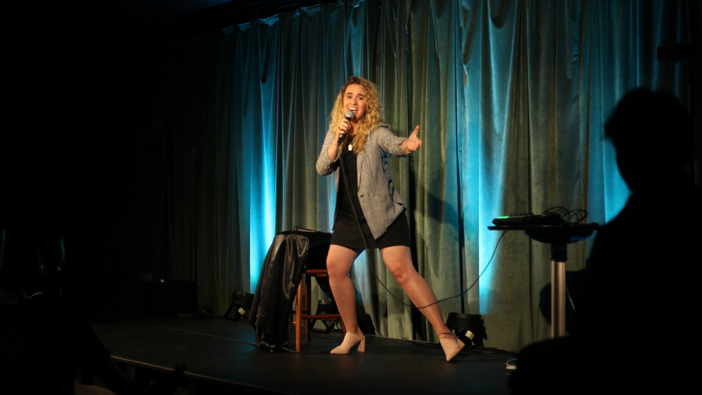 Michelle Braiser performing comedy with a microphone on stage