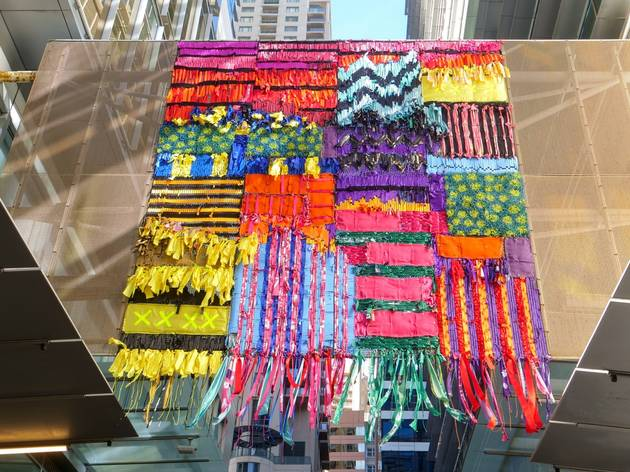 A beautiful, colourful woven sculpture made of old advertising material and flags hanging over World Square