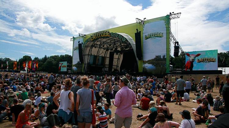 A crowd of people sitting and standing in front of a large outdoor stage with screens either side, on a sunny day at Latitude