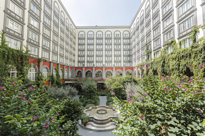 Jardín entre torres de un edificio con fuente al centro