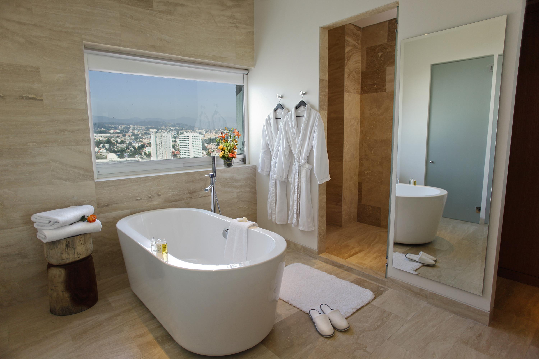 Interior de baño con tina, batas y ventana con vista a la ciudad