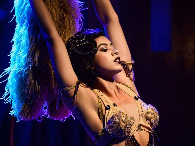Burlesque star Zelia Rose holds aloft a feather boa