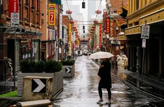 A woman wearing all black and holding a pale umbrella trudges across Little Bourke street in Chinatown