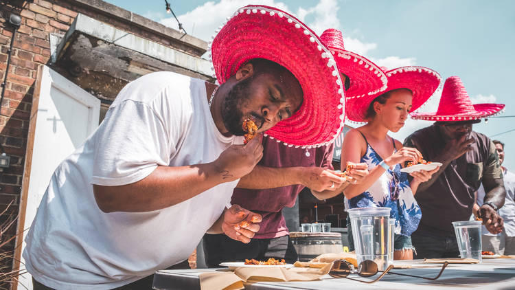 People eating wings in red sombrero hats
