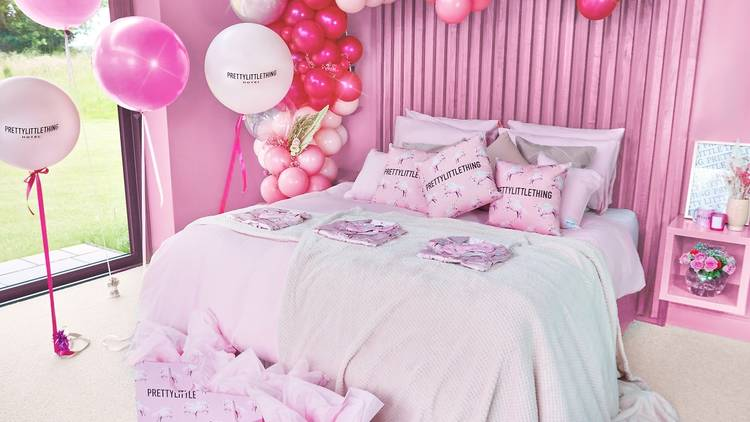 A bedroom with pink walls, cream carpet, a large pink double bed covered in Pretty Little Thing branded cushions, surrounded by pink and white balloons