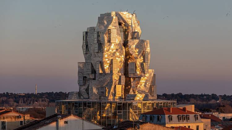 The Tower at LUMA looms over the town, with light from the setting sun reflecting off the stainless steel tiles that cover the structure