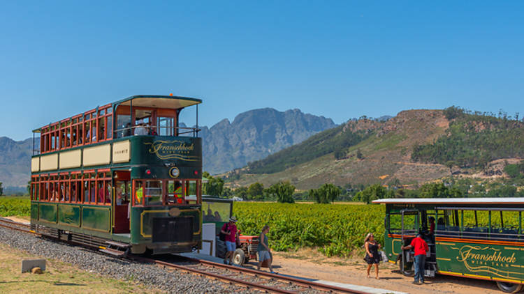 A green and red vinate double decker tram  running along a track in front of a mountainouse rocky background, with a bright clear blue sky above