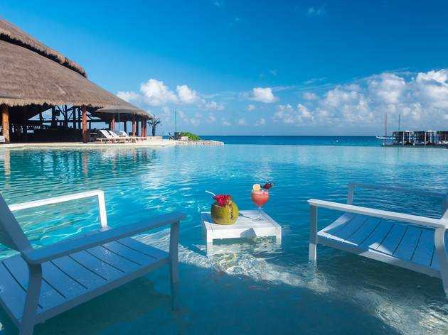 Infinity pool Hotel Presidente Intercontinental Cozumel con sillas en el agua